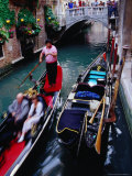 Gondola with Passengers Gliding Through Narrow Canal  Venice  Italy