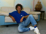 David Essex  Sitting on the Floor Leaning Against a Sofa Wearing Denim Jeans and Blue Top