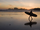 Surfer Walks Across the Beach at Sunset