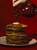 Hand Pours Syrup onto a Stack of Pancakes