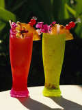 Two Tall Cold Tropical Drinks Garnished with Fruit and Flowers