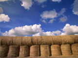 Cumulus Clouds Above Stacked Hay Bales in Saskatchewan