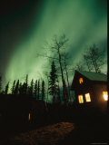 Aurora Borealis Fills the Sky over a Warmly Lit Cabin