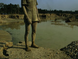 Gold Miner Standing Next To Runoff Pond Laced with Mercury and Cyanide