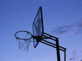 Tattered Basketball Hoop Silhouetted Against the Late Day Sky