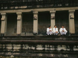 Three Cambodian Men in Suits Squat on the Temple Steps at Angkor Wat