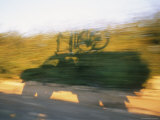 Fast-Moving Truck's Shadow with Bikes  Cast on Roadside Vegetation