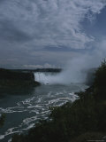 Distant View of Mist-Shrouded Niagara Falls Under a Cloudy Sky
