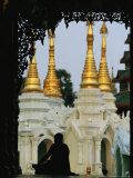 Silhouetted Monk Meditating Near Temple with Gilded Spires