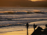 Surfers are Silhouetted by the Sunset on a Beach in Santa Barbara