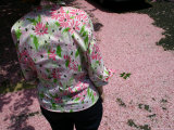 Real Fallen Cherry Blossoms Blend with a Floral Blouse