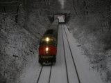 Train Approaches Through Falling Snow at Dusk