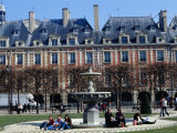 People Relaxing Around Fountain in Place Des Vosges