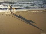 Woman Tending to Fishing Net on Beach Near Mui Ne