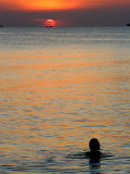 Sun Setting over Sea with Silhouette of Person Swimming