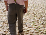 Rear of Man Walking on Cobbled Street
