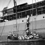 People Climbing Down a Ladder  Trying to Board an Already Overfull Lifeboat  as SS Zam Zam Sinks