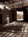 White-robed Man Walks under Thatched Canopy  Morocco