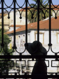 Tourist Gazes at Historic House through Iron Grillwork of Church  Lisbon  Portugal