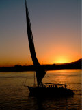 Felucca Silhouetted Against Setting Sun over the Nile at Luxor  Egypt