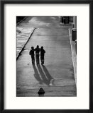 Three boys walking down street arm in arm