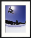 Airborne snowboarder in half pipe position