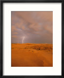 A bolt of lightning strikes the sand dune landscape