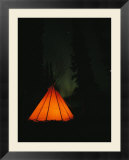 The glow from a campfire makes a shadow on a tepee