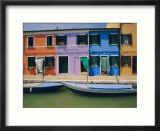 A view of the brightly colored buildings of Burano with gondolas floating at their doorsteps