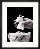 Female hand holding wedding cake topper