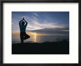 A woman practices yoga on the beach at sunset
