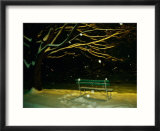 Snow falls on a park bench at night