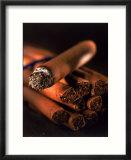 Lit cigar on top of bundle of cigars