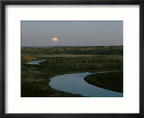 The moon rises over low hills banking the river