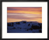 Sunset sky over snowy hills cast in shadow