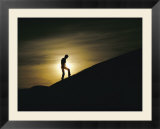Silhouette of a man walking up a dune against a cloudy sun