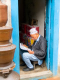 Hindu Man Reading Paper in Doorway of Bhaktapur  Kathmandu  Nepal