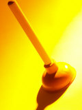 Red Rubber Plumbing Plunger in Yellow Light