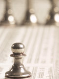 Selective Focus of Silver Pawn on Newspaper Stock Market Report with Line of Chess Pieces
