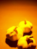 Selective Focus of Three Heads of Fresh Garlic on Orange Surface