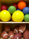 Colorful Balls and Footballs Arranged on Shelves of Wooden Storage Closet