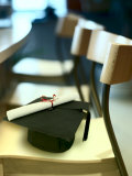 Graduation Cap and Diploma on Empty Wooden Chair