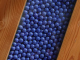 Pearly Cerulean Marbles Between Wooden Boards