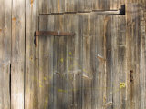 Weathered Wooden Door and Wall with Rusted Brass Hinge