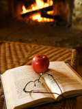 Relaxing Scene of an Apple and Eyeglasses on Open Book by Fireplace at Home