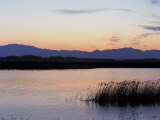 Sunset over a Peaceful Lake with Silhouette of Mountains
