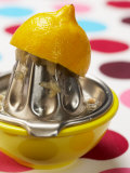 Juicer with Bowl and Lemon Half on Polka Dot Surface