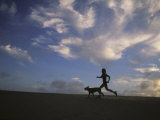 Woman and Her Dog Run Along the Beach with Beautiful Sky