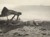 Two Women Lying on the Sea Shore in the Shade of a Towel