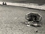 Young Couple  in an Amorous Embrace  Lying on the Beach on the Seashore